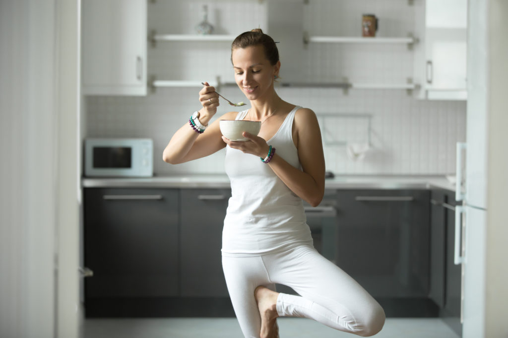 Sporty funny attractive woman having lunch in kitchen while practicing yoga, standing in Tree exercise, Vrksasana pose, work out in white sportswear, enjoying food, indoor, home interior background