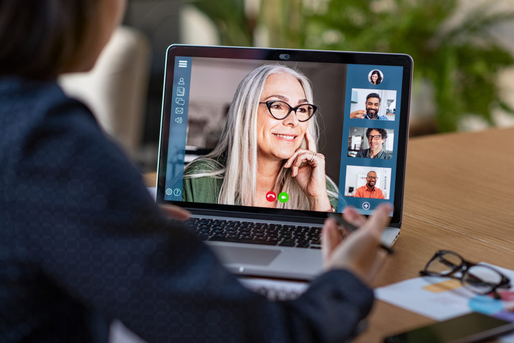 Multiethnic business team having discussion in video call. Rear view of business woman in video conference with boss and his colleagues during online meeting. Senior woman making video call with partners using laptop at home: remote job interview, consultation, human resources concept.