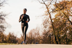 Full length of black sportswoman jogging during autumn day in nature.