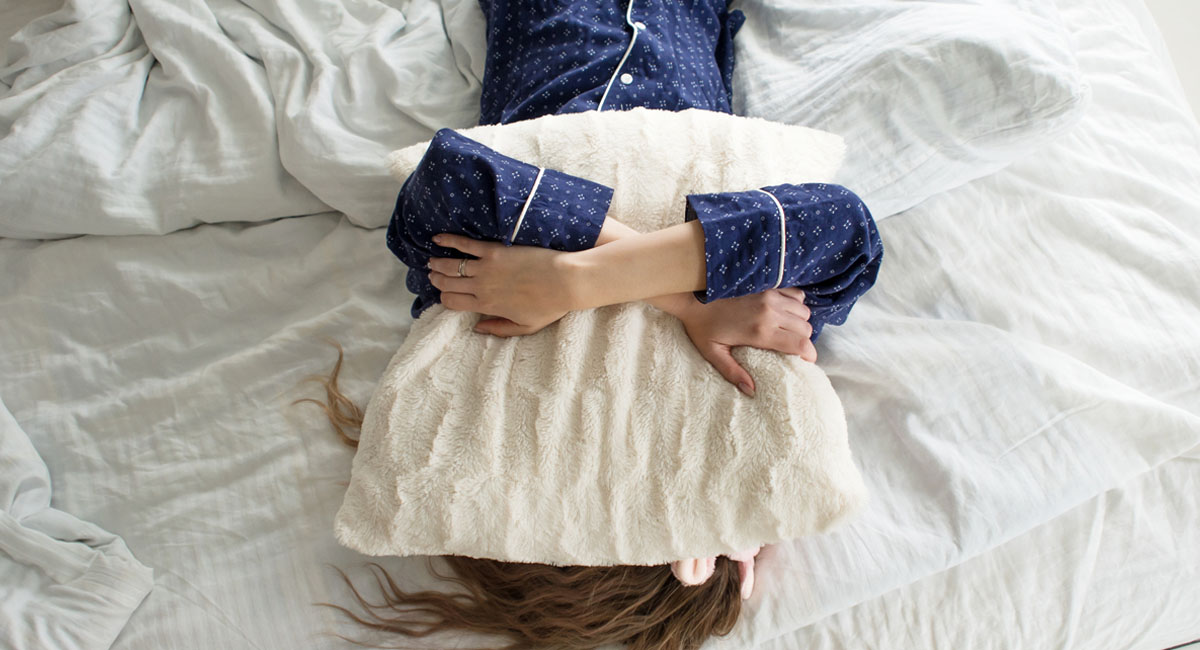 Lady trying to get over hangover laying in bed, covering head with pillow.