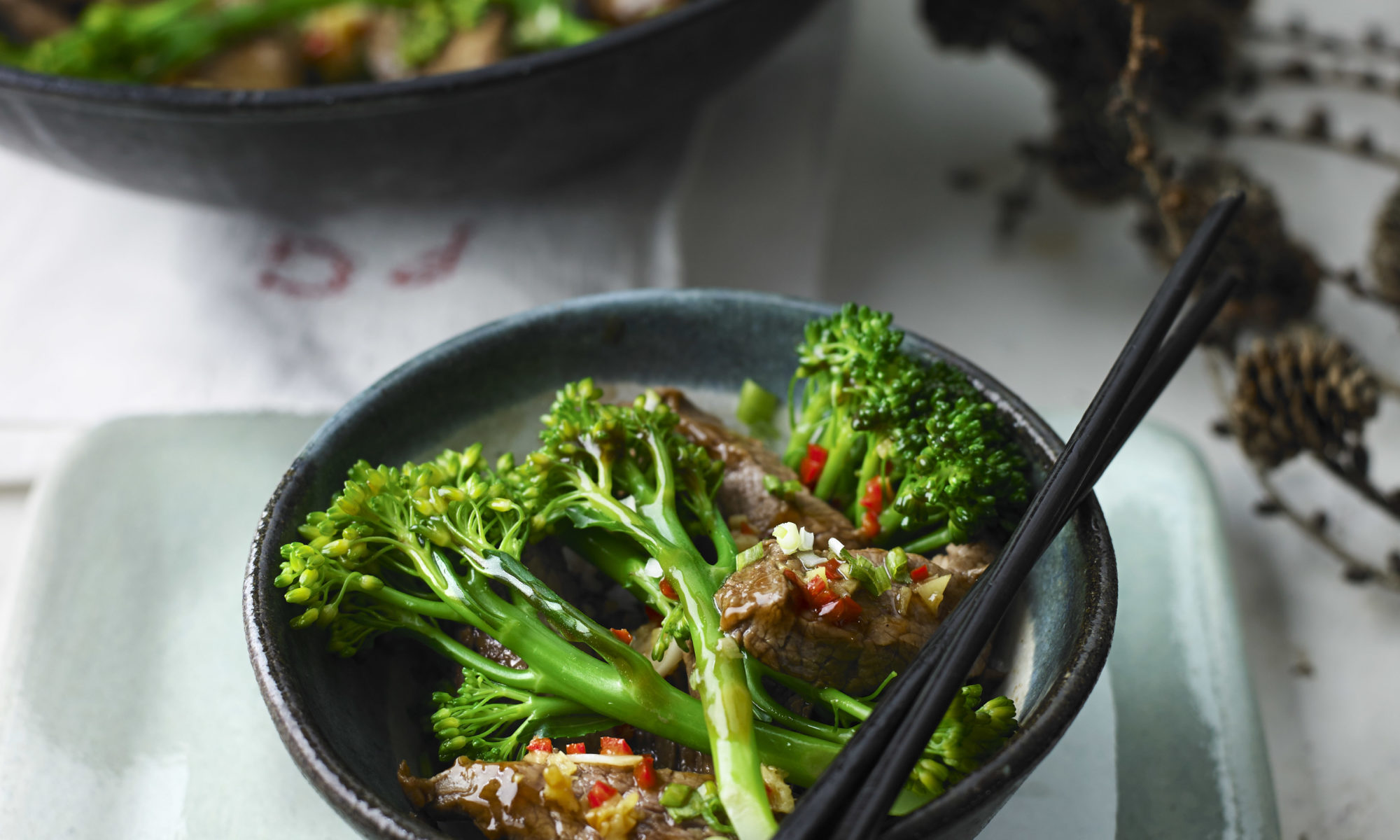 Beef & broccoli in oyster sauce in black dish with chopsticks.