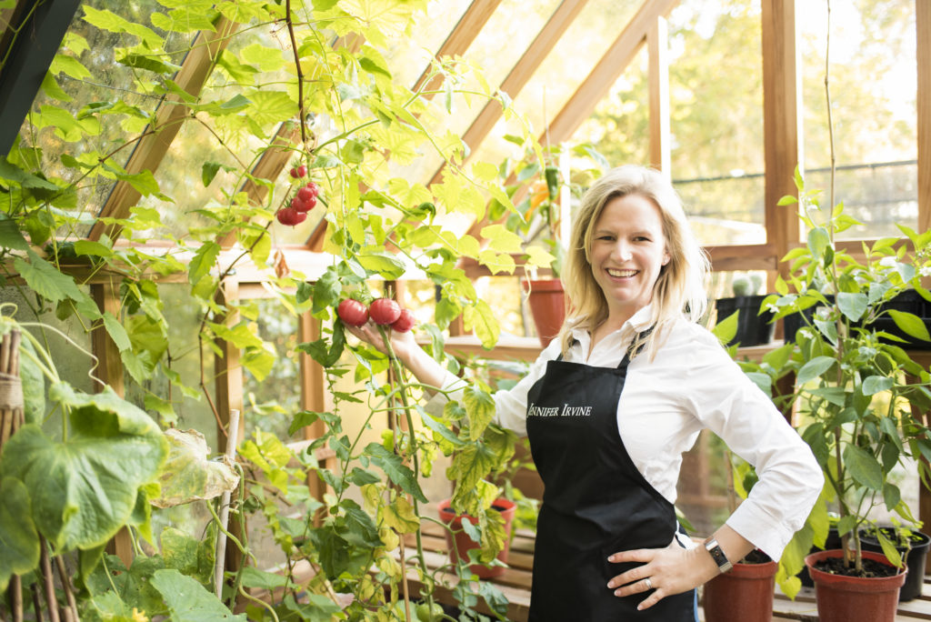 Jennifer Irvine in her greenhouse showing off home grown tomatoes