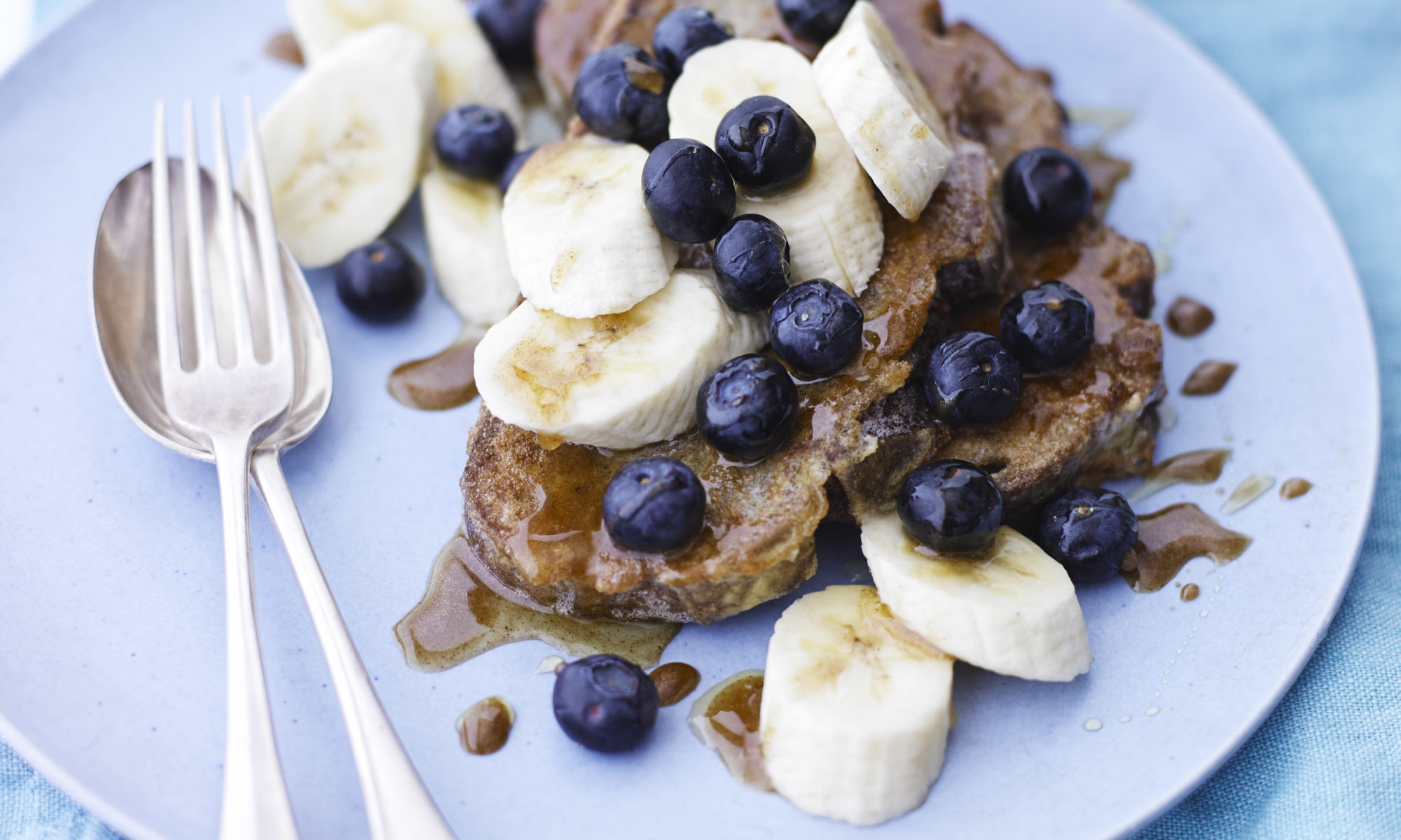 French toast with cinnamon honey with sliced banana and blueberries