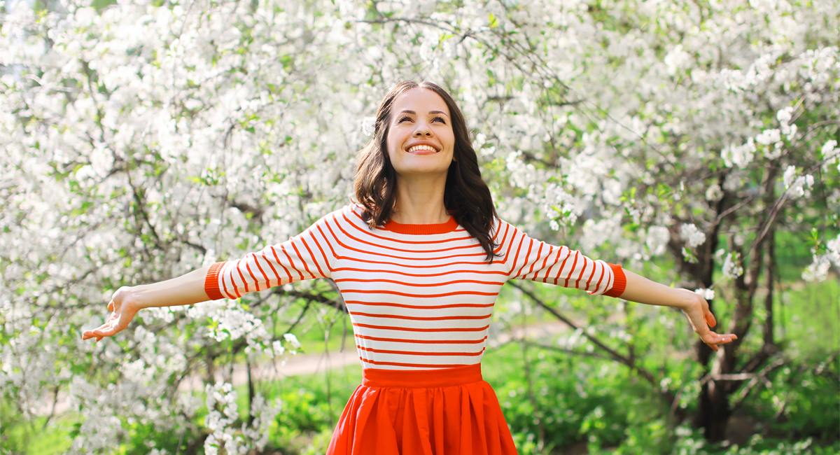 Beautiful happy young woman smiling in a flowering spring garden