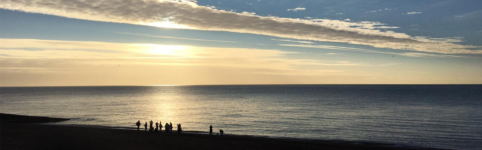 Silhouette of WOW members standing on the sea front in Hastings