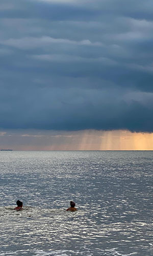 WOW members in the sea, with sun shinning through clouds